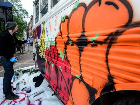 Derek Lindow, a local artist from Port Crane, spray paints a design onto the side of the CHOW Bus during Mural Fest 2014 on May 17.