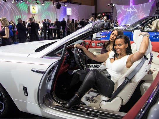 Gina Coleman of Beverly Hills, and her friend Lisa Mills pose for a photo in a Rolls-Royce Dawn during the Gallery held at Cobo Center.
