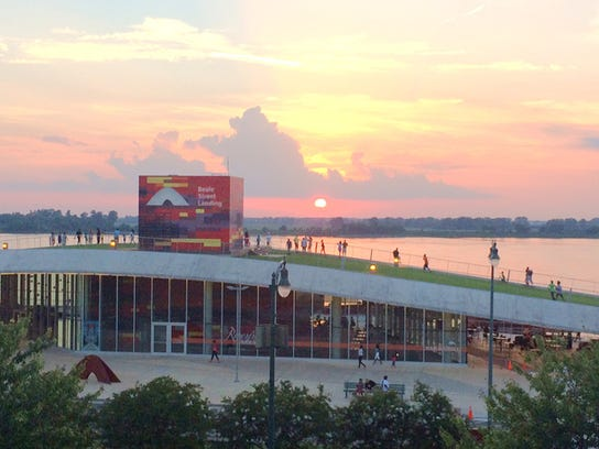 Visitors walk up and down the grassy slope of Beale Street Landing at dusk.