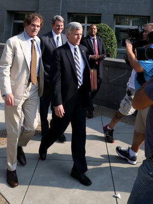 "Former Virginia Gov. Bob McDonnell, front, and lawyers Henry ""Hank"" Asbill, left, and John Brownlee, in background, leave the federal courthouse Aug. 5, 2014, in Richmond, Va., where the McDonnell's federal corruption trial ended its seventh day."