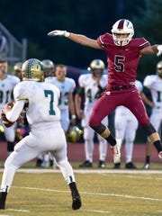 Milford's Seth Seelye (right) jumps high to distract