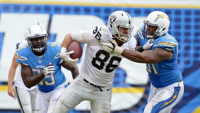 Oakland Raiders tight end Lee Smith (86) is defended by San Diego Chargers defensive end Kendall Reyes (91) on a run after a third quarter catch at Qualcomm Stadium.