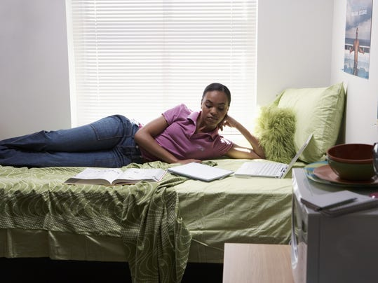 Young woman lying on bed with laptop and books in student dormitory