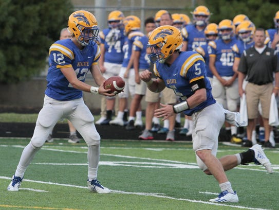 Paul Kremer of NewCath holds the handoff out to Kyle