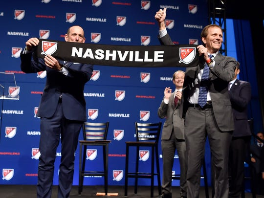 Major League Soccer Commission Don Garber holds up a team scarf with John Ingram, Nashville SC's lead investor, during the announcement of the new Major League Soccer franchise in Nashville at the Country Music Hall of Fame Wednesday, Dec. 20, 2017, in Nashville, Tenn.