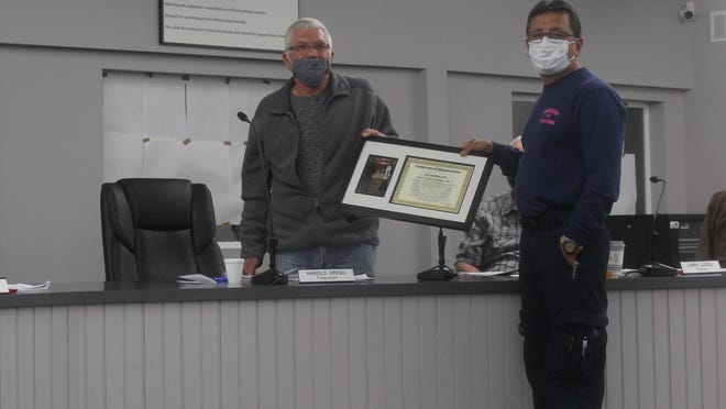 Madison Township Building Inspector David Rincon, right, is presented with a certificate of appreciation from treasurer Harold Gregg on Oct. 13. Rincon was awarded the certificate for his work in bringing Hampton Manor, an assisted living facility, to the township.