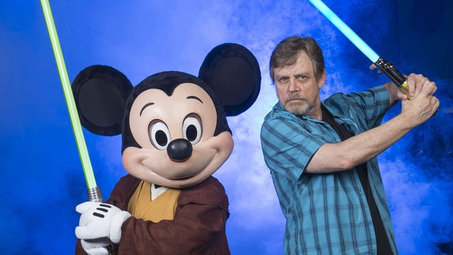 """LAKE BUENA VISTA, FL - JUNE 05:  In this handout photo provided by Disney Parks, actor Mark Hamill, who portrayed Luke Skywalker in the 'Star Wars' film saga, poses with Jedi Mickey Mouse at Disney's Hollywood Studios June 5, 2014 in Lake Buena Vista, Florida.  Hamill is at the Walt Disney World Resort theme park for appearances June 6-8 at """"Star Wars Weekends,"""" an annual special event.  This year marks the first time Hamill has attended 'Star Wars Weekends' in the event's 17-year history.  (Photo by David Roark/Disney Parks via Getty Images) ORG XMIT: 496547111 ORIG FILE ID: 450106170"""