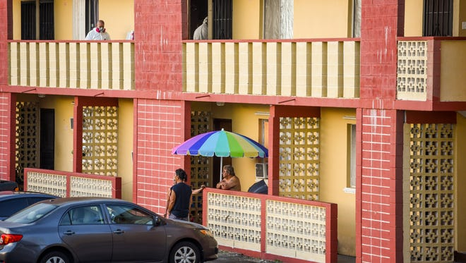 Apartment complex residents hang out on a first floor balcony as Guam Police Department officers and forensic technicians, some wearing protective coveralls and using respiratory protection masks, conduct a death investigation in a unit above at the Taitano Rentals in Mangilao on Wednesday, July 18, 2018.