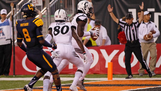 UC's Tion Green (7) scores a touchdown in front of Toledo's Chaz Whitaker during the first quarter Friday at Paul Brown Stadium.