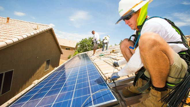 Solar installer Dylan Robins wires a panel on top of a home in Cave Creek. More customers moving to solar could have an impact on people who own stocks in utilities.