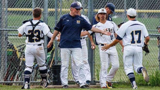 Kettle Moraine head coach Jim Wilkinson congratulates players on a successful inning during the game at home against Waukesha North on Wednesday, July 5, 2017.