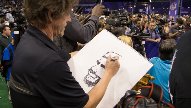 The Arizona Republic cartoonist Steve Benson draws a caricature of Seattle Seahawks QB Russell Wilson during Super Bowl Media Day at U.S. Airways Center in Phoenix January 27, 2015. The Patriots will play the Seattle Seahawks Sunday February 1 in Super Bowl XLIX in Glendale.