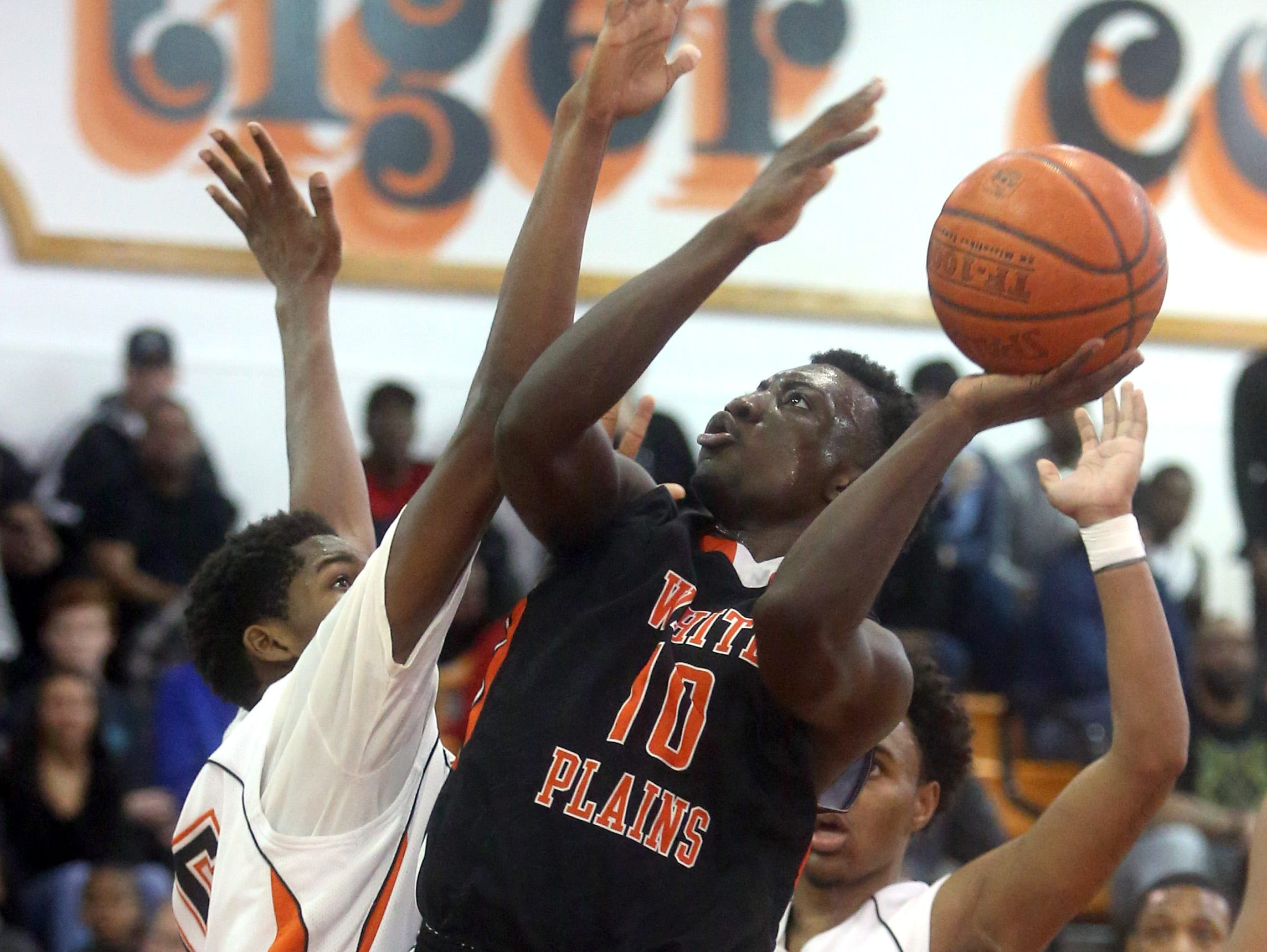 Lamar Noel of White Plains shoots over Mavenson Therneus of Spring Valley during a Class AA quarterfinal basketball game at Spring Valley High School Feb. 201, 2015. White Plains advanced to the Westchester County Center with an 85-78 victory.