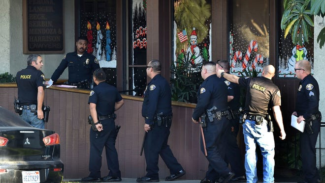 """Police officers gather in front of law offices where a deadly shooting took place in Long Beach on Friday, Dec. 29, 2017. Long Beach police on Friday called the shooting """"workplace violence."""" They said on Twitter that it has become a murder investigation, and that the suspect is also dead at the scene."""