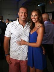 From left, Indianapolis Colts' Matt Overton and Breanna Fonner pose for a picture together during Pat McAfee's Red, White and Boomstick charity cocktail gala, at the Indianapolis Regional Airport, Friday, June 26, 2015, Greenfield, Ind.