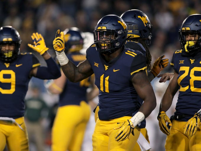 FILE - In this Oct. 25, 2018, file photo, West Virginia linebacker David Long Jr. (11) celebrates with teammates after sacking Baylor's quarterback during the first half of an NCAA college football game, in Morgantown, W.Va. David Long Jr. was selected defensive player of the year when the AP All-Big 12 team was announced Friday, Dec. 7, 2018. (AP Photo/Raymond Thompson, File)