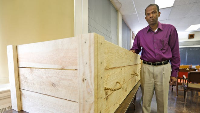 Rev. Alfred L. Jones III poses with a period style pine box coffin that will be used to represent former slave Hannah Reynolds, who was the lone civilian death at Appomattox at the end of the war, at the Carver-Price Legacy Museum in Appomattox, Va., Wednesday, April 1, 2015. Jones will deliver the eulogy for Reynolds whose death will be remembered during the 150th anniversary of the Civil War's end. (AP Photo/Steve Helber)