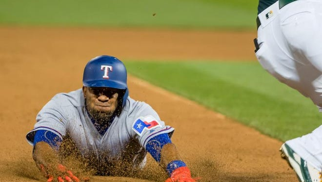 Rangers shortstop Elvis Andrus (1) steals third base against Oakland Athletics third baseman Trevor Plouffe (3) during the sixth inning at Oakland Coliseum.  Andrus has four steals. Oakland won, 4-2.