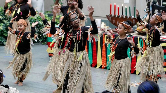 Anaheysha Baptiste, 11, center, and the Avenue D Recreation Center dancers perform during a Kwanzaa celebration at the Memorial Art Gallery in Rochester on Dec. 29, 2013.