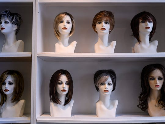 A wall of wigs are displayed for customers at The Cottage Wig Shoppe located on Second Street in downtown Henderson, Ky., Wednesday, May 30, 2018. Customers are encouraged to touch and try on as many wigs as they want. They can also order custom hair colors through the shop.