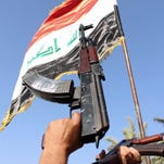 Iraqi tribesmen carry their weapons as they gather to show their willingness to join Iraqi security forces.