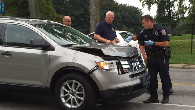 Officers gather evidence from the vehicle suspected in multiple hit-and-runs in downtown Indianapolis on Wednesday, Aug. 26, 2015.