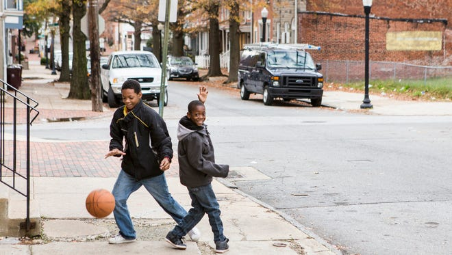 Thirteen year-old Walter Potter (left) plays basketball with his cousin, eight year-old Dedrick Ford outside Potter's grandmother's house in West Center City on Sunday afternoon.