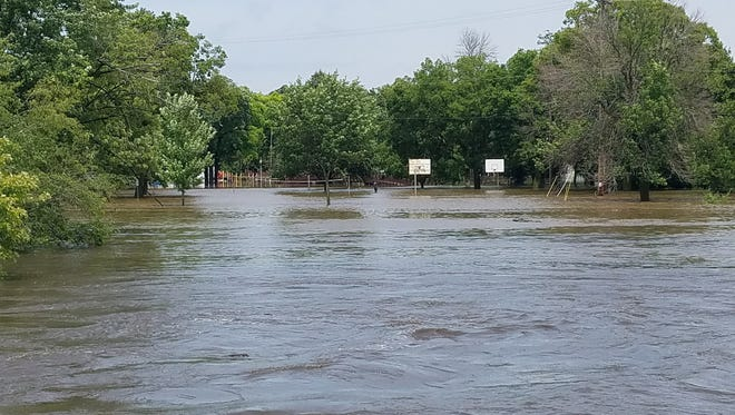 Basketball hoops and volleyball nets half underwater as flooding continues in Burlington.