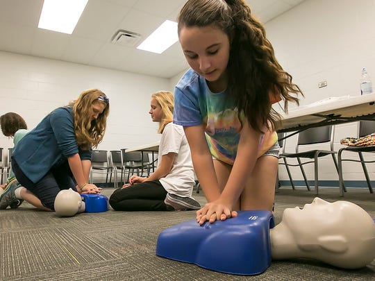 Natalie Bryson, Sydney Reeder and Lydia Hicks work on their CPR skills during Ultimate Baby Sitting Camp at Sports*Com.