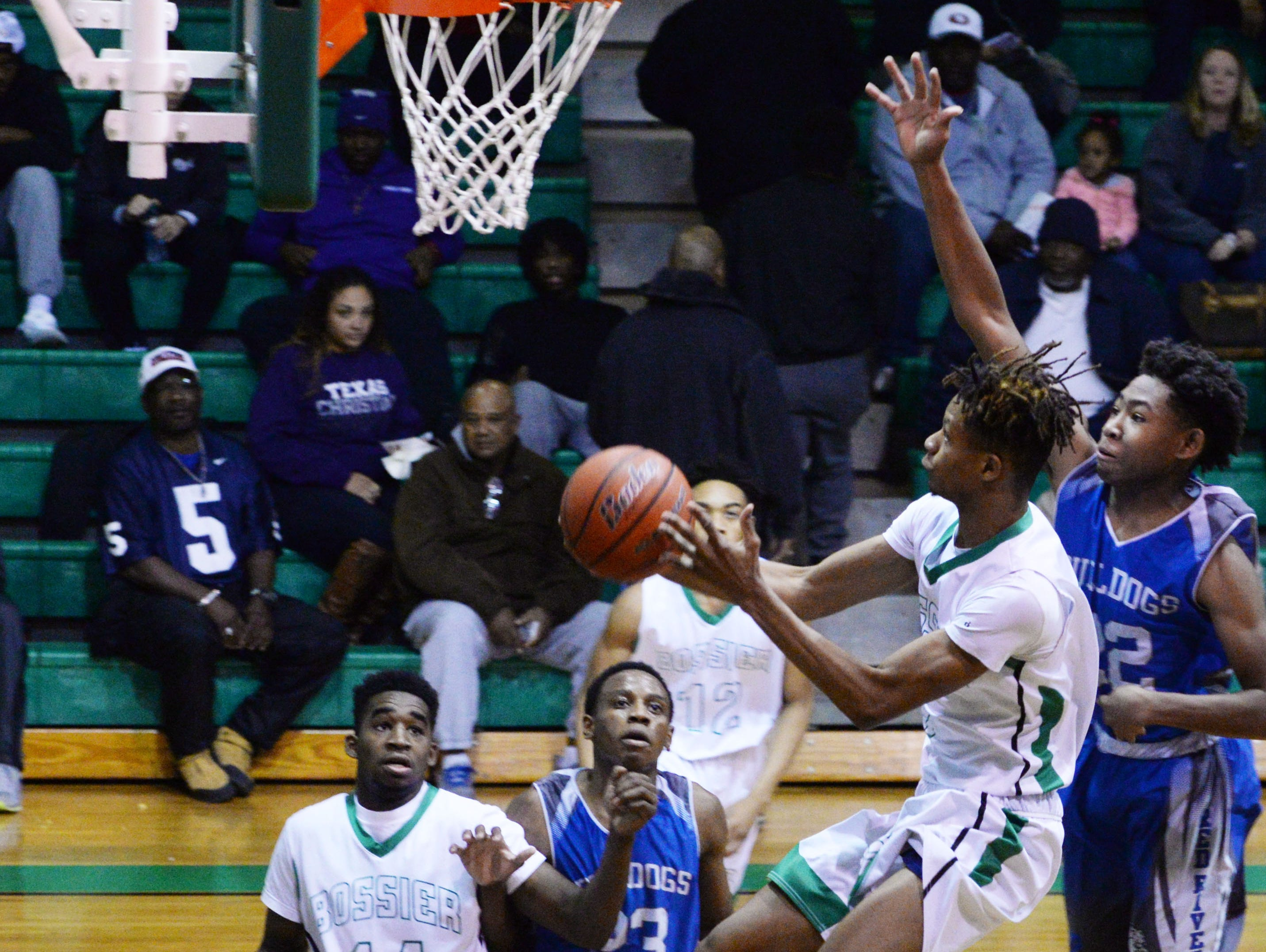 Bossier's TyBo Wimberly tries to get the ball in the basket during their game against Red River Friday evening.