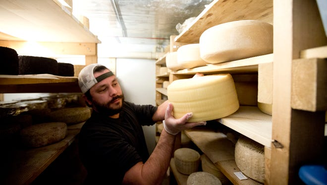 Drew Bristol checks on a cheese called equinox at a facility at Camphill Village at Kimberton Hills in Phoenixville, Pa., rented by Birchrun Hills Farm. Many small farmers must increasingly rely on community relationships and higher product quality.