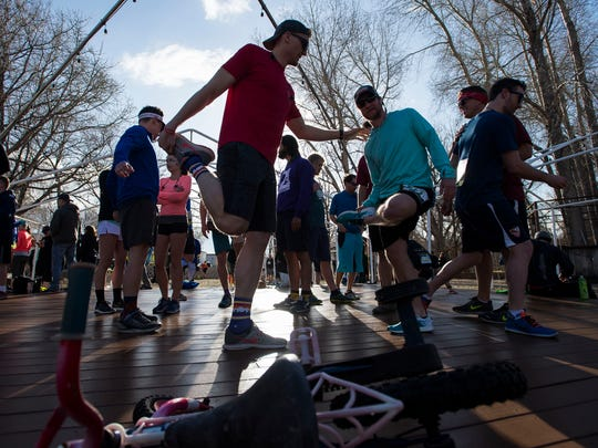 Sean Nielsen, left, and Logan Bell help each other limber up with other friends of Jake Lord, a CSU graduate that dies in a climbing accident on Capital Peak in July, before the Horsetooth Half Marathon on Sunday, April 15, 2018, in Fort Collins, Colo.