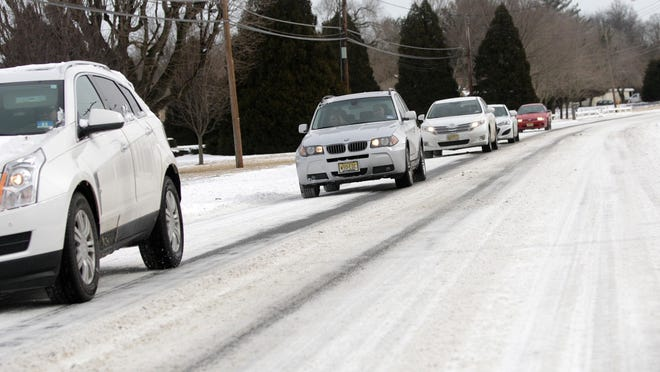 Cars travel slowly on East Oak Road in Vineland on Monday. Snow that fell Saturday night into Sunday morning is still on the road, as well as many other local roads, making driving difficult. More snow was forecasted for Monday night into Tuesday morning.