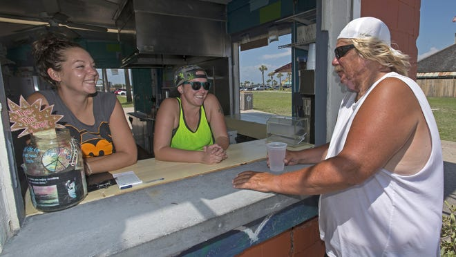 Lisa Bryan, left, and Tia Tucker, center, talk with regular customer Denny Cugburn, right, at the new eatery on Pensacola Beach called The Stand. The Stand, opened in late spring of this year, occupies the iconic two-story structure at Casino Beach known to most local residents as Tiffany's.