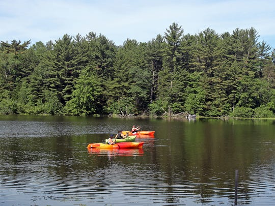 Kayakers paddle on Mirror Lake in the state park of the same name.