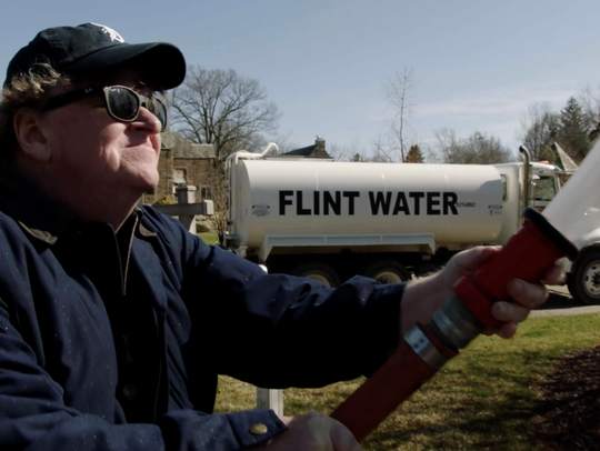 "Michael Moore sprays ""Flint water"" at the Michigan State Capitol building in Lansing in his documentary ""Fahrenheit 11/9."""