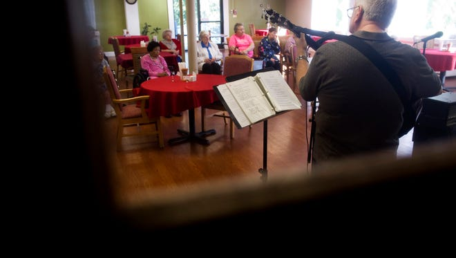 DENNY SIMMONS / COURIER & PRESSCliff Furgerson of Evansville strums along with a gospel music group at Bethel Manor Sunday afternoon, Oct. 10, 2015. Furgerson and his wife, Laura, were hospitalized after a tornado tore through Eastbrook Mobile Home Park on Nov. 6, 2005. Laura Furgerson later died from complications from her injuries. Cliff Furgerson's pastor laid claim to his Dean accoustic guitar after someone found it after the storm inside a pickup truck with its back window broken out. When Furgerson went to play it, the guitar was not only unscathed, but still in tune. Furgerson now uses a Fender guitar since retiring his Dean.