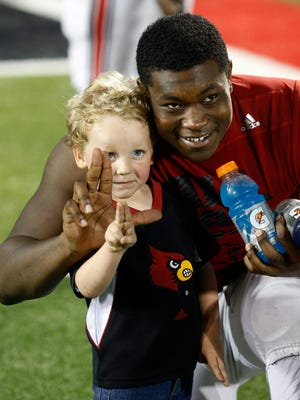 Louisville's Isaac Stewart works with Liam Spalding on how to throw up an 'L.'  April 17, 2015