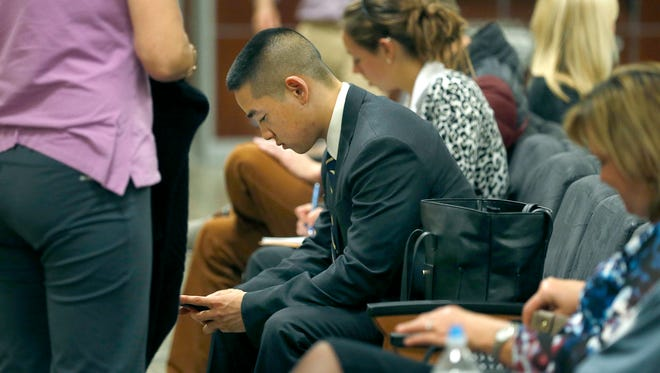 Charles Tan waits with friends outside of court on the seventh day of jury deliberations Wednesday, Oct. 7, 2015.