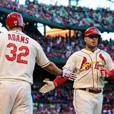 St. Louis Cardinals left fielder Matt Holliday (7) is congratulated by first baseman Matt Adams (32) after hitting a solo home run off of Colorado Rockies starting pitcher Franklin Morales (not pictured) during the first inning at Busch Stadium.