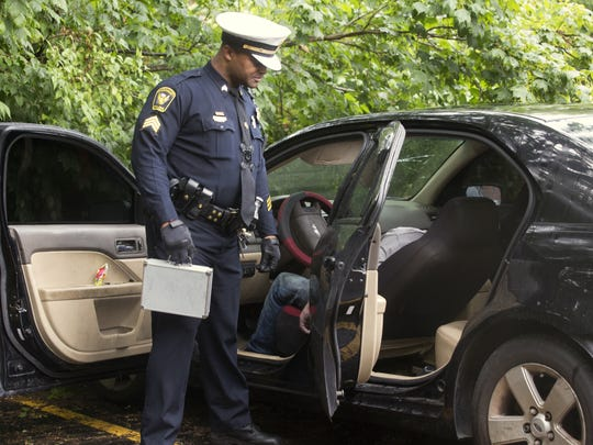 Cincinnati Police Sgt. Ken Hall checks the body in a Ford Fusion in the back parking lot of an apartment in Epworth in Westwood. Residents had called the police about a person unresponsive in a car. The cause of death was suspected overdose.