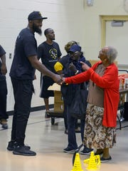 Pro basketball free agent Reggie Evans is thanked by greatful recipiants of free turkeys Saturday during the Reggie Evans Foundation Annual Turkey Giveaway at the Woodland Heights Resource Center. Reggie gave away 400 turkeys with stuffing and green beans..