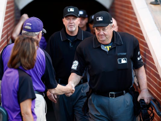 Crew chief Joe West, right, is congratulated as he heads to the field to umpire his 5,000th career game as the Colorado Rockies host the Arizona Diamondbacks in the first inning of a baseball game Tuesday, June 20, 2017, in Denver. (AP Photo/David Zalubowski)