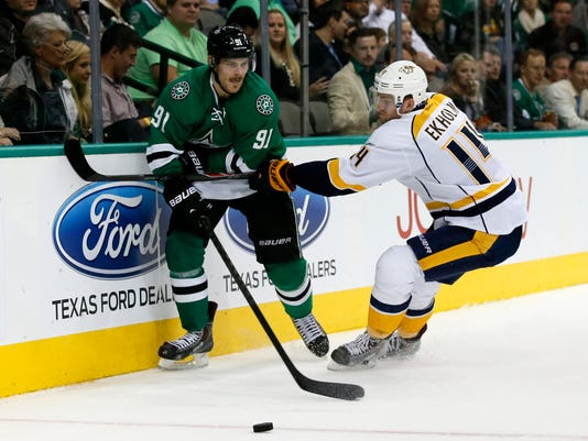 Dallas Stars' Tyler Seguin (91) and Nashville Predators' Mattias Ekholm (14) compete for control of the puck during the first period of an NHL hockey game, Thursday, Nov. 6, 2014, in Dallas. (AP Photo/Tony Gutierrez)
