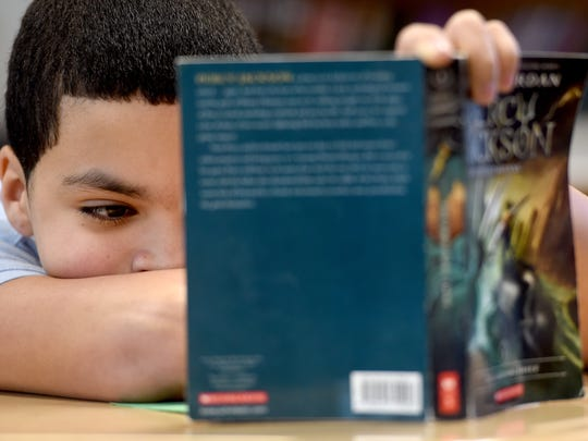 """Xavier Feliciano, a fifth grader at Jackson K-8 school, follows along with his class as they read """"Percy Jackson."""" Work on a new recovery plan in York City School District has so far included having staff members and consultants rewrite the English language arts and math curriculum."""