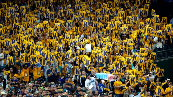 """Fans in the """"King's Court"""" cheering section for Seattle Mariners starting pitcher Felix Hernandez hold up K-cards as they cheer for a strikeout as Hernandez pitched during the seventh inning of a baseball game against the Texas Rangers, Saturday, April 18, 2015, in Seattle."""