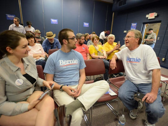 """Molly Lucio, 25, and her husband, Anthony Lucio, 26, both of Muscatine, Iowa, discuss Bernie Sanders with Bob Handel, 62, of Davenport, on Friday at Muscatine Community College. The Lucios said they attended the meeting because they are """"huge supporters"""" of Sanders. Handel said, """"He's the real deal."""" All three said they would caucus for Sanders."""