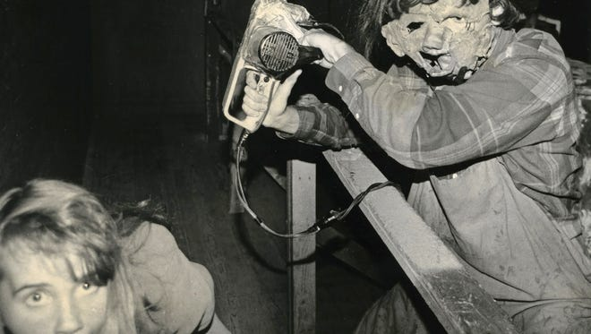 A patron of the Dungeons of Doom encounters a chainsaw-wielding killer in this 1991 photo.