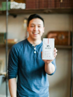 Nam Nguyen holds a bag of Archive Coffee Roasters coffee.