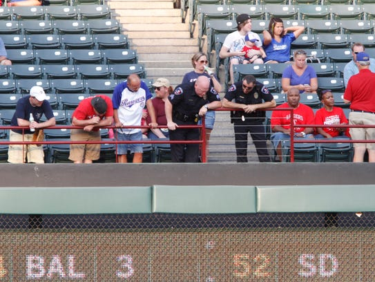 Police and fans look over the railing where fan Shannon